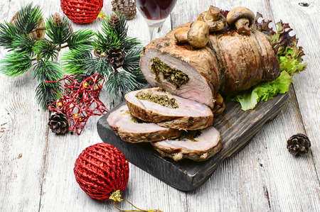 Dish of roulade of veal stuffed with mushrooms and spices and Christmas decorations