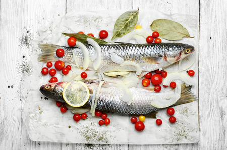 Two carcasses of raw marine fish in seasonings and tomatoes