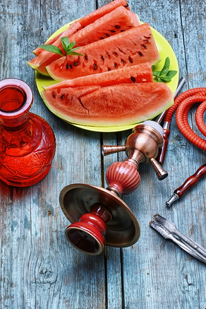 smoking pipe: Details Eastern Smoking hookah and diced ripe watermelon