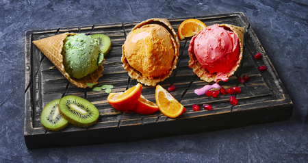 Summer ice cream assortment of fruit flavors with kiwi and pomegranate