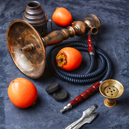 Smoking hookah with the tobacco flavor with the taste of ripe persimmons