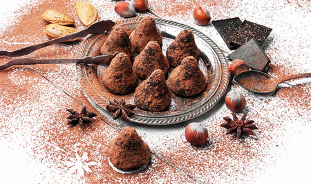 Chocolate truffles candies with cocoa powder and nuts.
