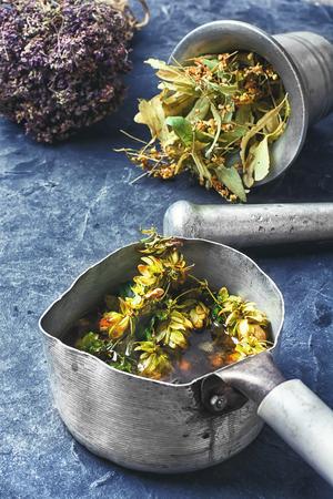 healer: Iron dipper with medicinal decoction of hop cones.