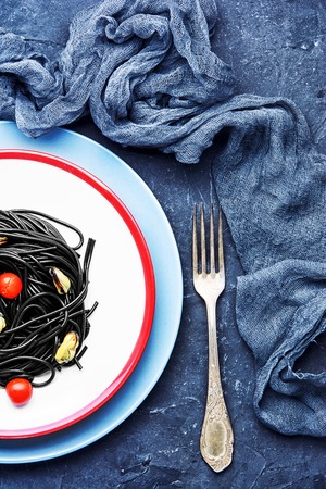 plate of spaghetti with black mussels and tomatoes.