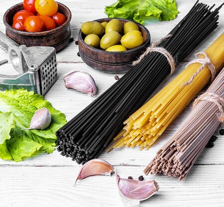 uncooked spaghetti and macaroni on the kitchen table with ingredients. Stock Photo