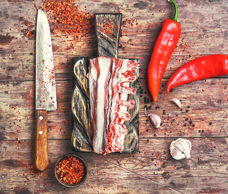 raw meat on the rib of lamb in hot spices on the kitchen board