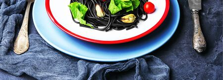 plate of black spaghetti with black mussels and and trout. Stock Photo