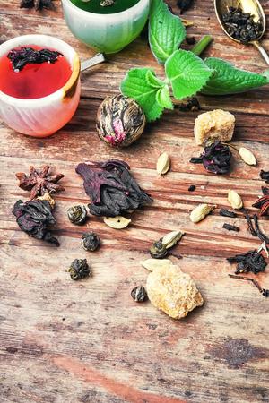 various types of fragrant herbal tea on vintage wooden background