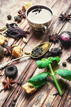 various types of fragrant herbal tea on vintage wooden background.