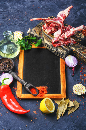 Raw meat on the rib of lamb in hot spices on the kitchen board.Copy space. Stock Photo
