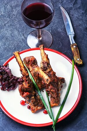 Dish of lamb chops baked in spices and glass of red wine. Stock Photo