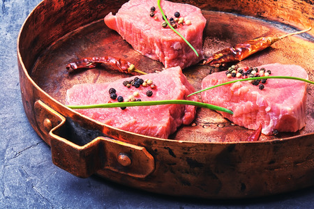 fillet of beef in spices, vintage copper pan.
