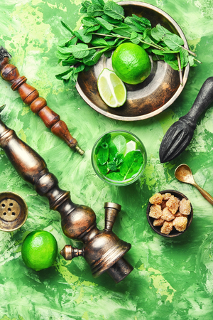 Smoking hookah with taste of the alcohol Mojito cocktail with lime and mint. Stock Photo