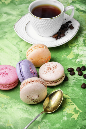 coffee and colorful French macaroons on green background