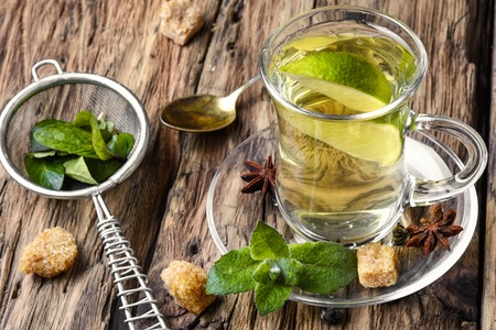 Tea brewed with lime and mint on wooden background Stock Photo
