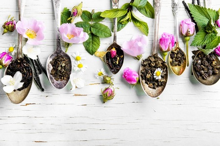 assortment of herbal teas in tea spoons on wooden background