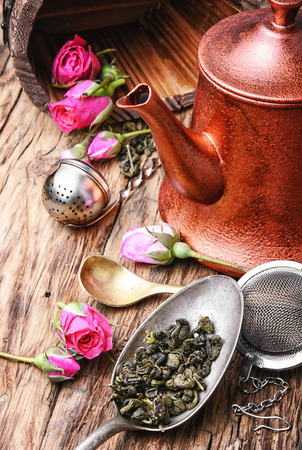 Stylish copper kettle, tea rose buds and dry tea leaf