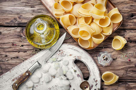 macarrones: macaroni with ingredients for cooking pasta on wooden table