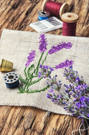 Embroidery bouquet of lavender and tools of needlework Stock Photo