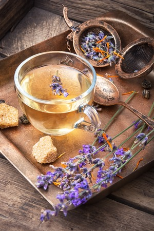 Herbal tea with inflorescence lavender in a glass cup in a rustic style