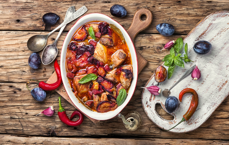 meat stew in a sauce of autumn plums on a retro background Zdjęcie Seryjne