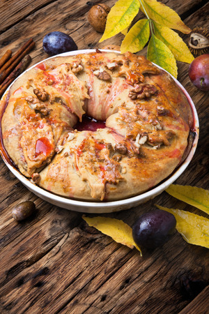 Plum strudel on background with autumn leaves Stock Photo
