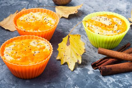 Pumpkin muffins on a background with autumn leaves