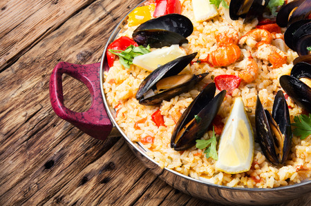 typical: vegetable paella with seafood on wooden background