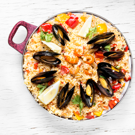 vegetable paella with seafood on wooden background