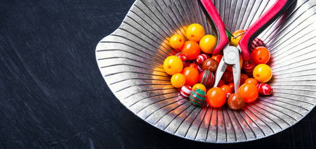 Orange plastic beads for needlework in a stylish tray