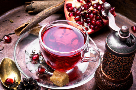 Cup of tea with pomegranate on retro rustic background