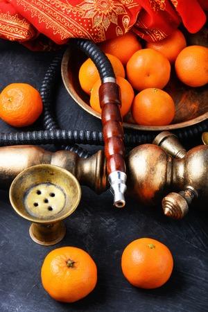 Smoking smoking shisha in east style with tobacco aroma of mandarin.