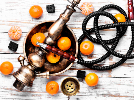 Smoking shisha in east style with tobacco aroma of mandarin.