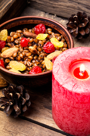 Traditional Christmas porridge, kutya and lighted candle Stock Photo