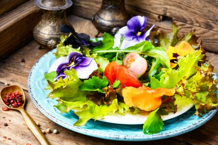 Fresh summer salad with edible flowers and herbs.Healthy food
