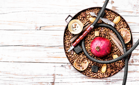 Smoke hookah with with coffee beans and pomegranate.Shisha concept.Hookah concept.Copy space Stock Photo