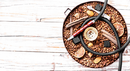 Smoke hookah with with coffee beans and pomegranate.Shisha concept.Hookah concept.Copy space Reklamní fotografie