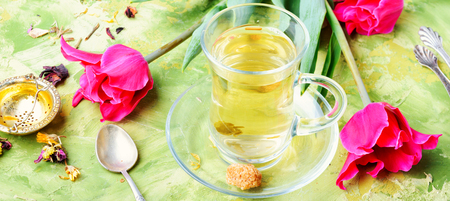 Cup with fragrant tea and spring pink tulips Stock Photo