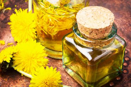 Bottle of essential oil with flowers dandelions.Healing herbs.Dandelions tinctures