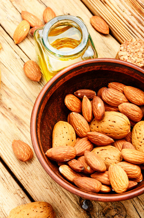 Almond oil in glass bottle and almonds on retro table.Almond massage oil