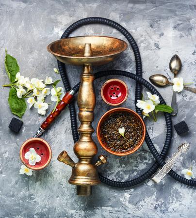 Smoke hookah with jasmine floral scent.Shisha concept.Modern hookah Stock Photo