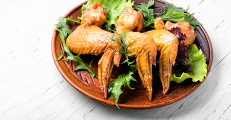 Smoked chicken wings and leaf salad. Fast food Stock Photo - 103619406