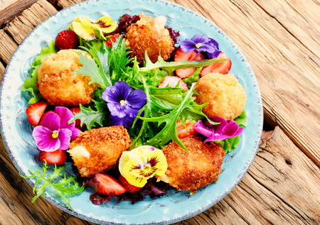 Vitamin summer salad with strawberries, grilled cheese, arugula and flowers.Healthy food Stock Photo
