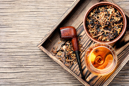Glass of cognac and pipe with tobacco Reklamní fotografie - 105291540