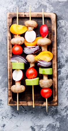 Grilled vegetable kebabs on skewers with tomato, pepper, mushrooms,zucchini and onion.Vegan diet.Vegetables kebab Фото со стока