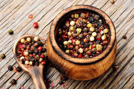 Assortment of peppercorn in the pepper box on a wooden background