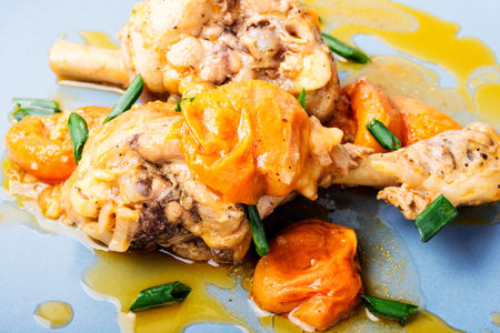 Chicken stewed in apricot sauce. Summer meat dish 스톡 콘텐츠