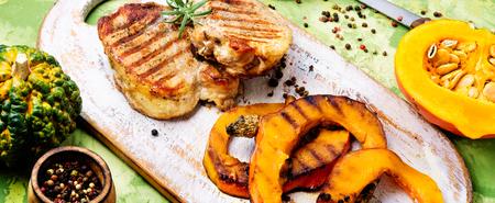 Baked meat with pumpkin on cutting board.Steak with pumpkin Standard-Bild