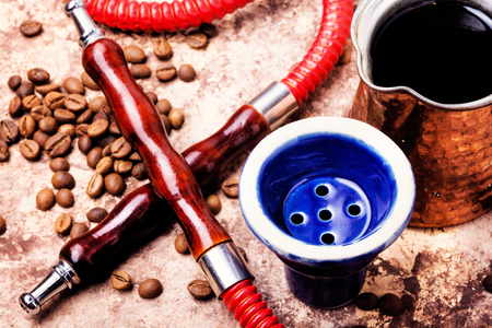 Stylish coffee jezva with coffee and hookah mouthpiece.Arabian shisha and coffee.Shisha Concept
