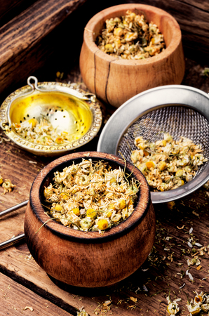Dried chamomile flowers for herbal tea.Medicinal herbs.Bowls of dry medicinal herbs